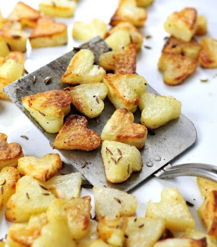 Cut your potatoes into flat discs, then use your smallest heart-shaped cookie cutter to cut out individual hearts before tossing them into your skillet with some olive oil.